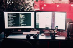 Dva monitora na stolu.